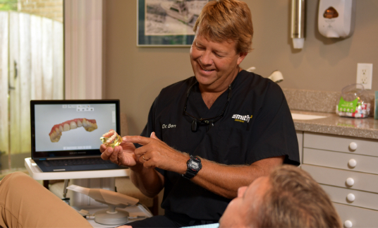 Image Dr. Ben Smith talking to a patient about veneers in Wilmington, NC.